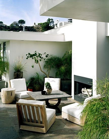 Modern Outdoor Seating Area with Fireplace and Potted Plants.