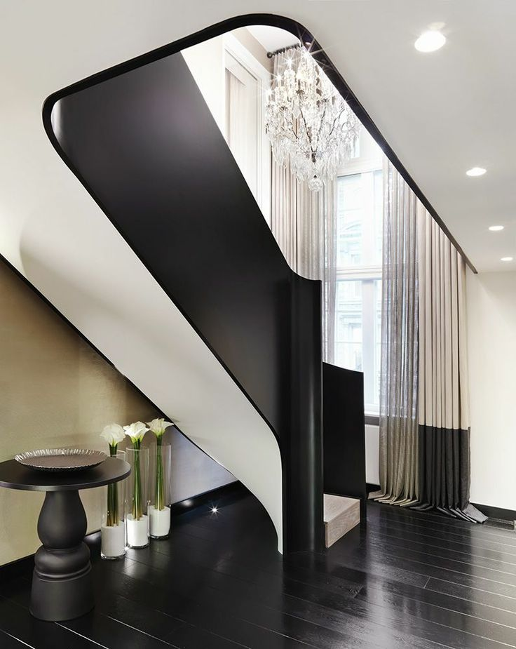 Landing - black and white staircase - dark flooring by Kelly Hoppen Interiors