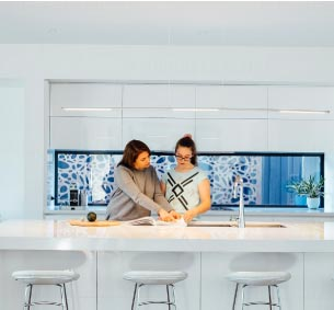 A mother and daughter reading a book on their white marble kitchen counter