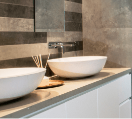 two round basins sitting on top of a stone top bathroom bench