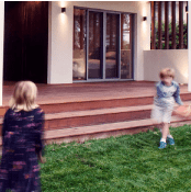 Two kids are playing in the garden of their new custom home built by Destination Living