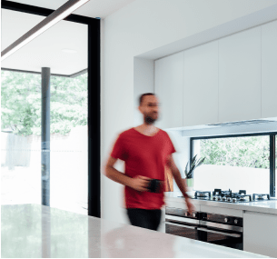 A man walks with a mug through his new kitchen built by Destination Living