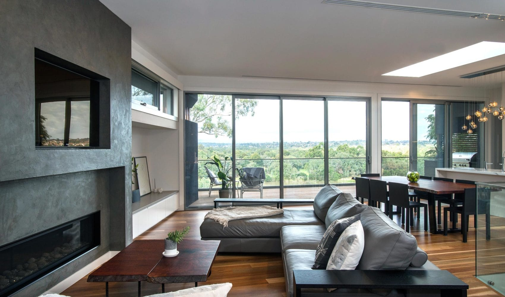 A modern living room built by Destination Living, containing a couch, coffee table, dining table, looking out a large window into the greenery beyond.